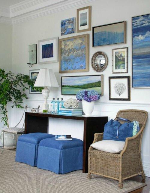 Много картин на стене в гостиной