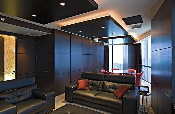 Многоуровневое освещение комнаты с черным диваном